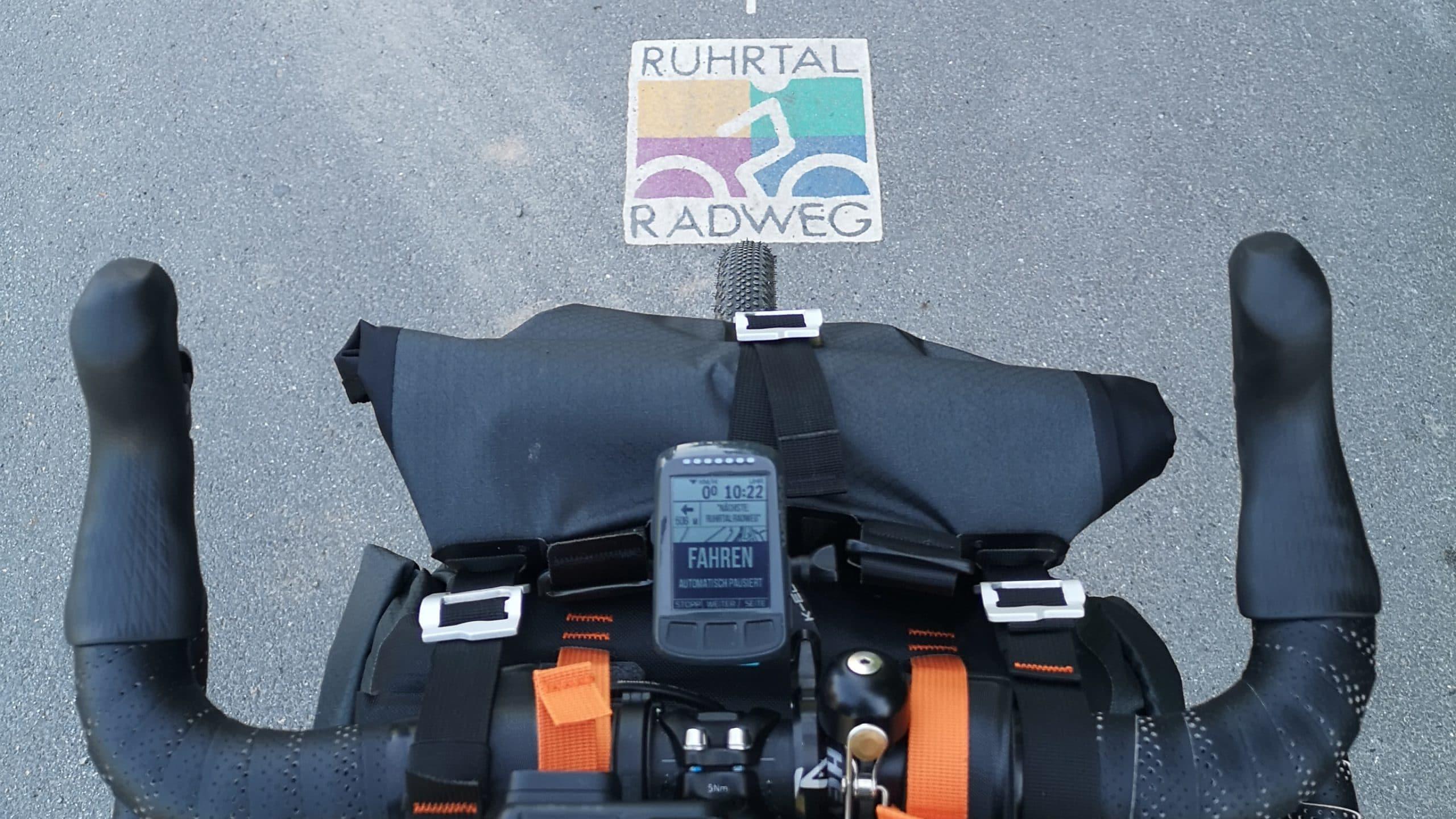 Fahrradlenker über einer Ruhrtalradweg Markierung